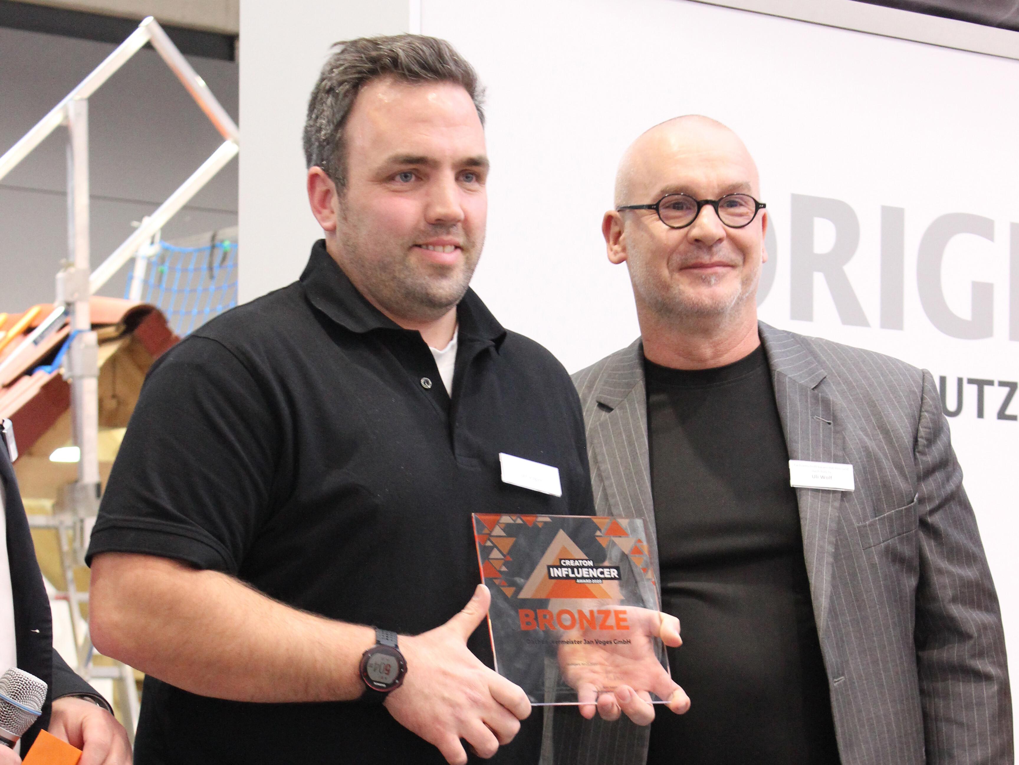 Der Drittplatzierte, Dachdeckermeister Jan Voges, mit Laudator und dach-holz.tv-Moderator Uli Wolf.