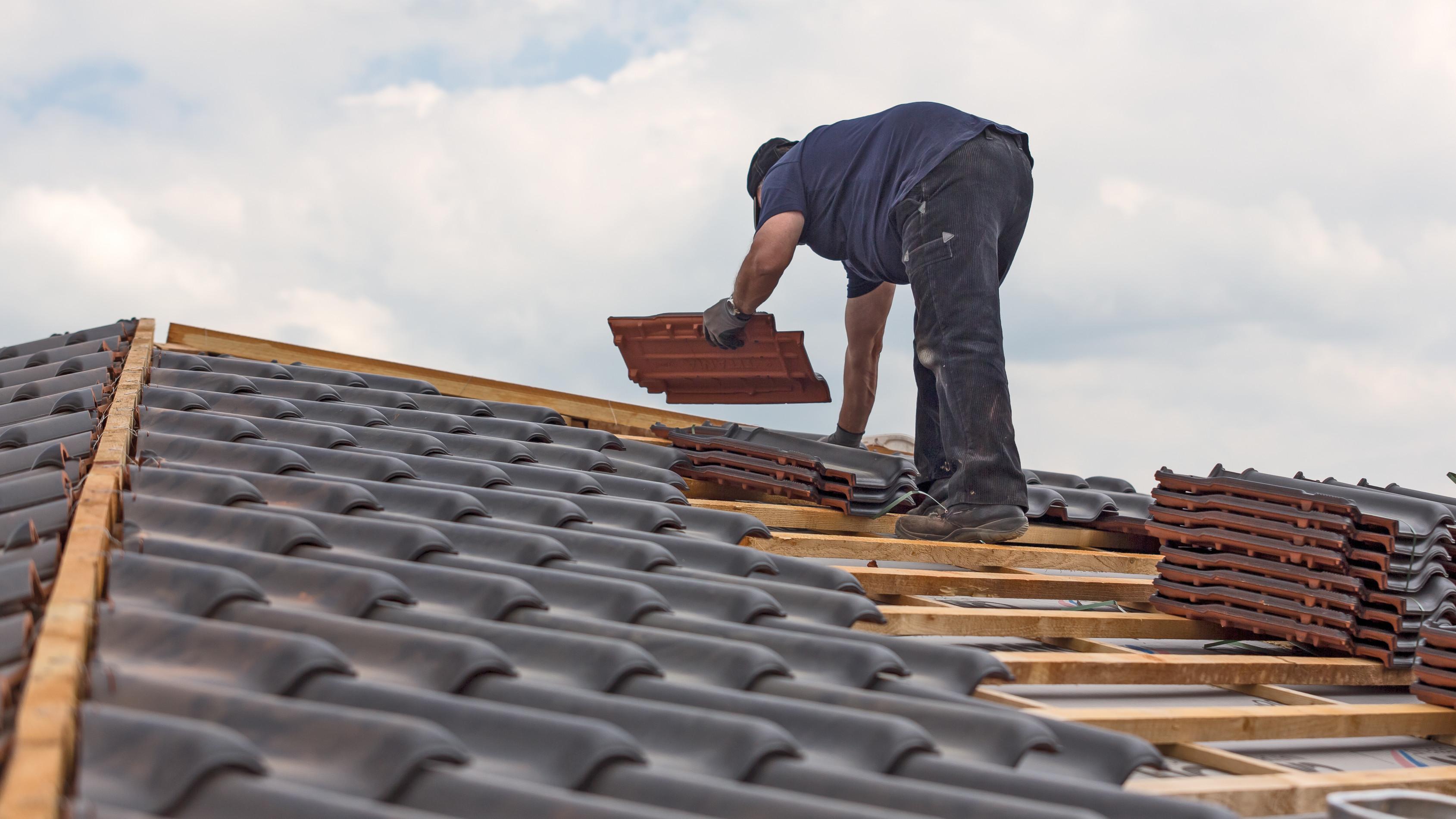 Dachdecker deckt Dach